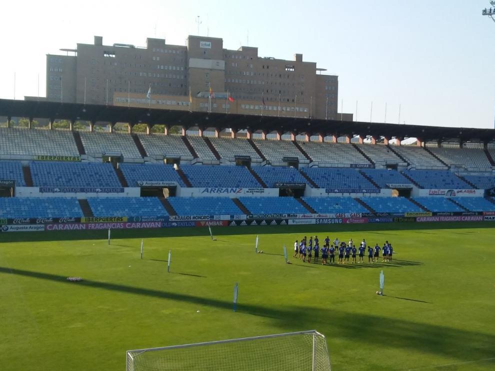 La reducida plantilla del Real Zaragoza, al inicio del entrenamiento de este jueves en La Romareda.