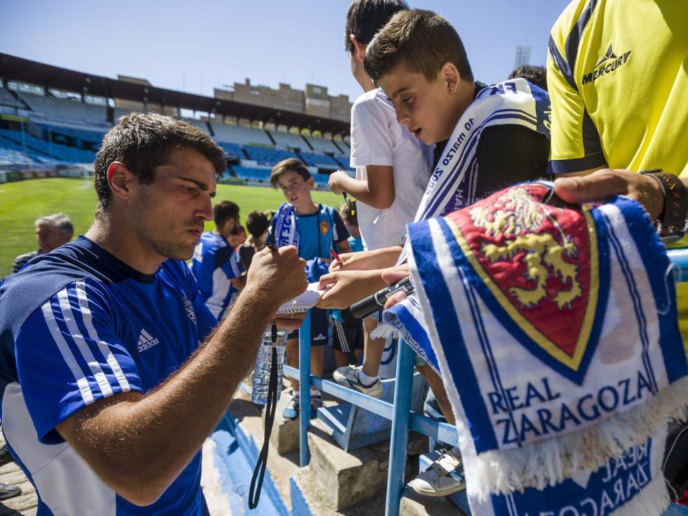 Zapater firma  autógrafos a unos jóvenes seguidores zaragocistas tras un entrenamiento en La Romareda.