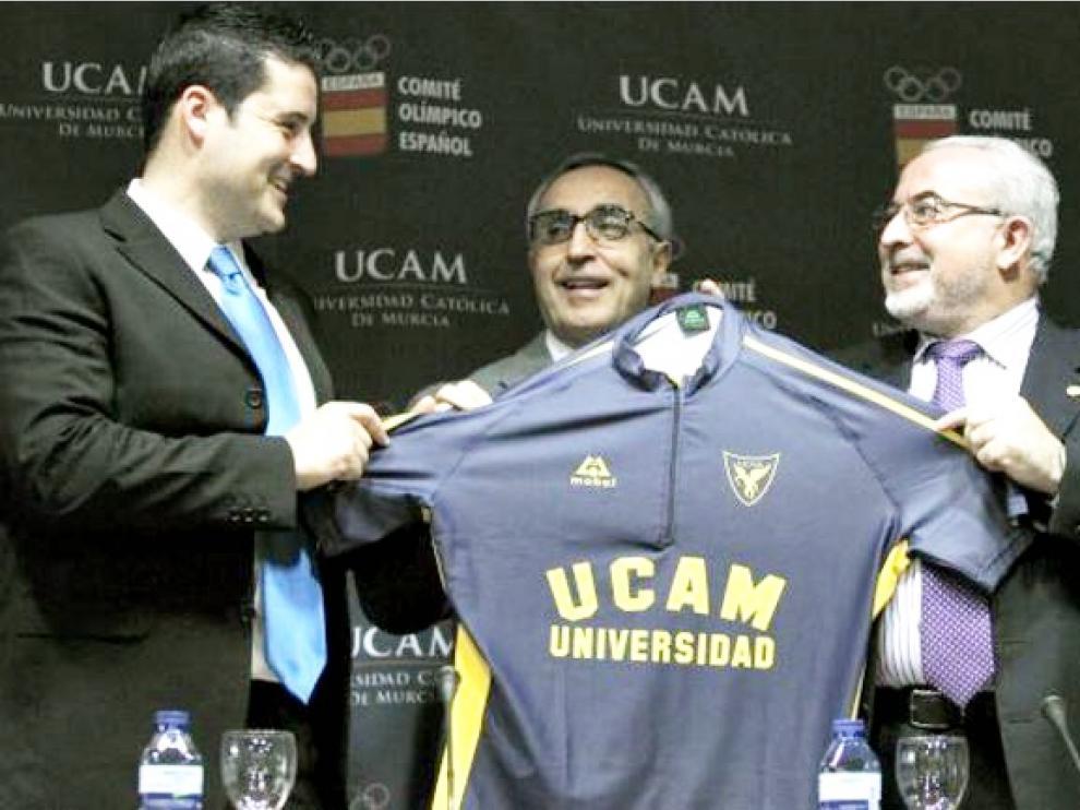 José Luis Mendoza (a la derecha), presidente de la UCAM, entrega una camiseta de su club al piragüista olímpico David Cal (izda.) en presencia de Alejandro Blanco (centro), presidente del Comité Olímpico Español.
