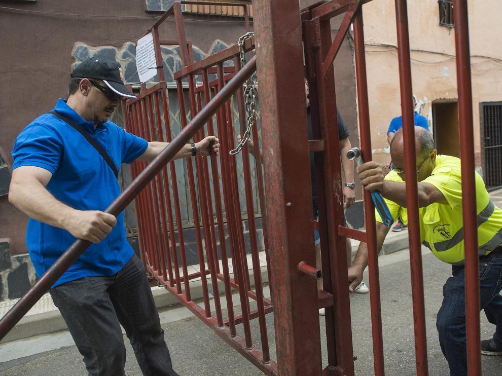 Cierre de las barreras. A la izquierda, uno de los voluntarios de la comisión de festejos y a la derecha, un alguacil del municipio cierran una de las barreras principales de la calle Mayor de El Burgo, una hora antes de que empiece el encierro.