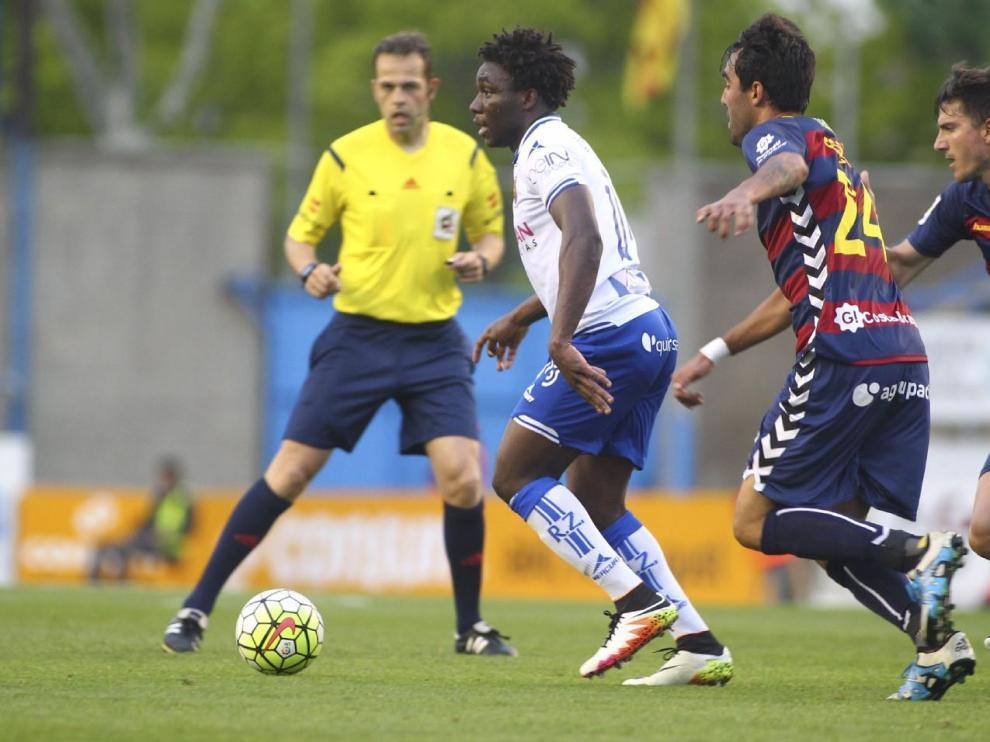 El árbitro Jorge Valdés Aller, en segundo plano, observa una jugada de Dongou ante dos rivales del Llagostera en el partido final de la pasada temporada, el 4 de junio en Palamós.