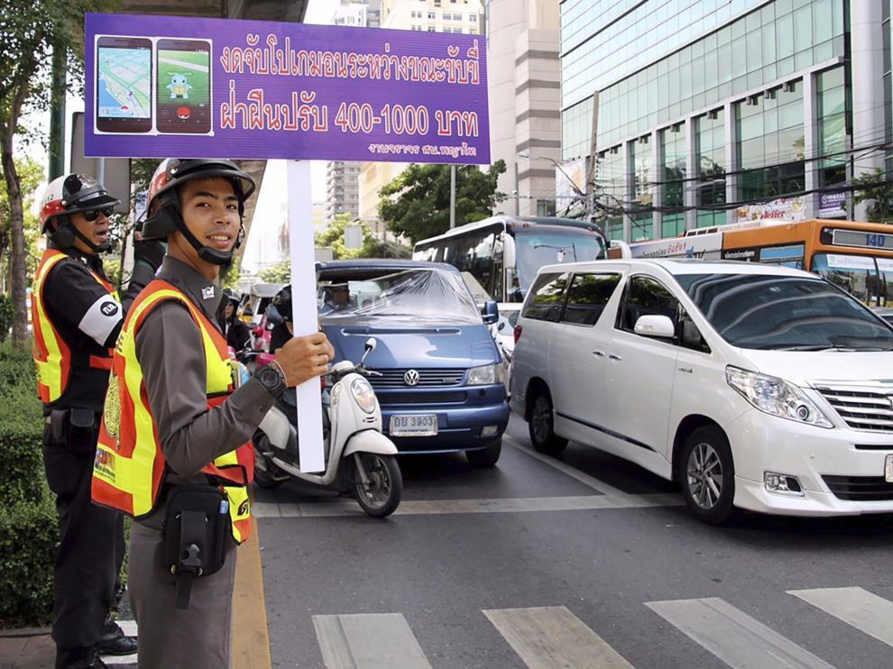 Un agente sostiene un cartel en el que se recuerda que está multado jugar mientras se conduce.