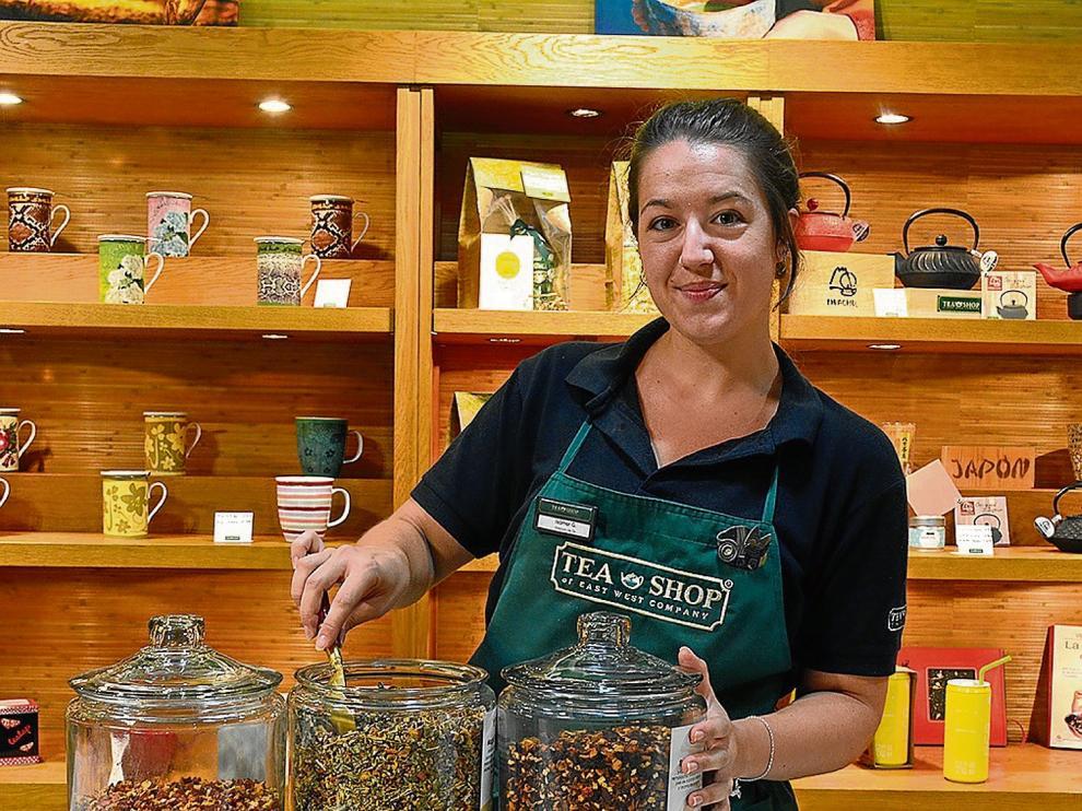 Isamar Gutiérrez, una de las dependientas de Tea Shop en el Coso de Zaragoza, con tres variedades de té.