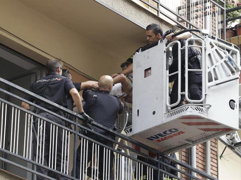 Efectivos de la Policía Nacional sacan de la vivienda por una escalera de Bomberos a uno de los jóvenes que han sido detenidos en Salamanca
