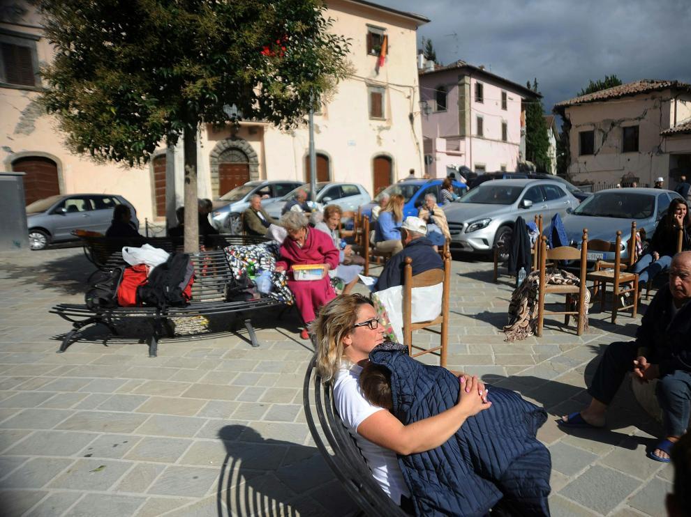Vecinos de Accumoli sentados en una plaza tras el terremoto que ha asolado el centro de Italia.