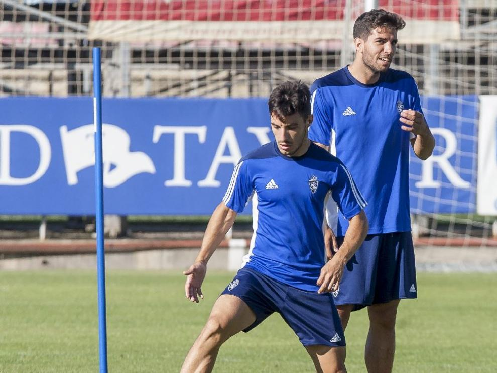 Leandro Cabrera, detrás de Isaac, durante el entrenamiento del Real Zaragoza este miércoles en la Ciudad Deportiva.