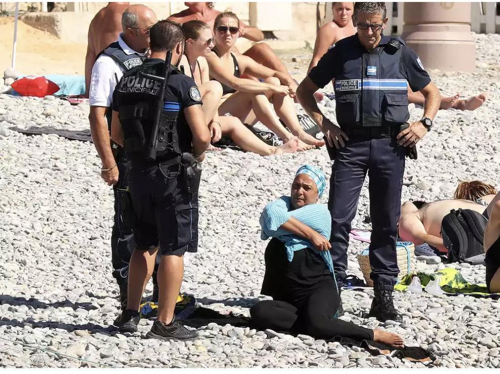 La policía obliga a una mujer a quitarse el burkini en una playa de Niza.