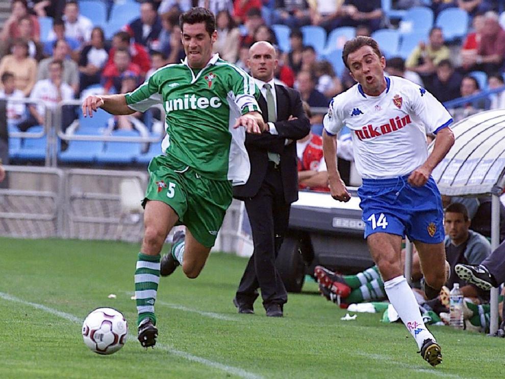 Luis César Sampedro, en segundo término delante de su banquillo en La Romareda, el 6 de octubre de 2002 en un Real Zaragoza-Racing de Ferrol. Juanele intenta desbordar al defensor gallego.