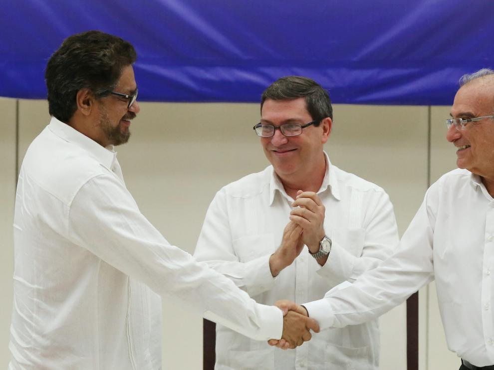 El jefe negociador de las FARC, Iván Márquez, y el del Gobierno de Colombia, Humberto de la Calle, se estrechan la mano tras el acuerdo.