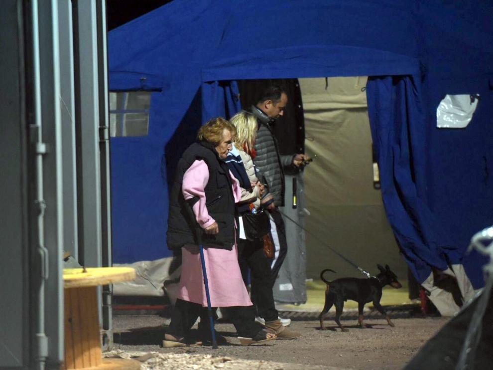 Afectados y voluntarios caminan junto a una de las tiendas instaladas en la localidad de Pescara del Tronto.