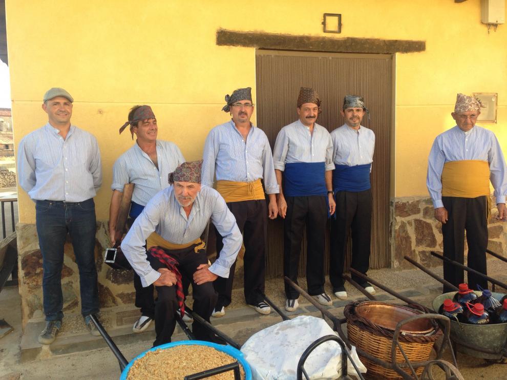 Los vecinos usaron trajes y elementos tradicionales para el reparto de las migas y el vino.