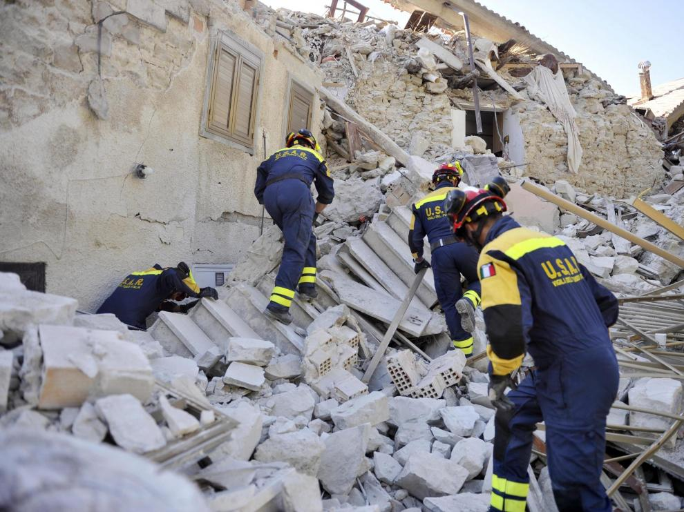Varios bomberos trabajan entre los escombros en Pescara del Tronto