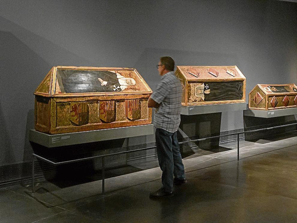 Un visitante contempla las tres cajas sepulcrales de Sijena expuestas en Lérida.