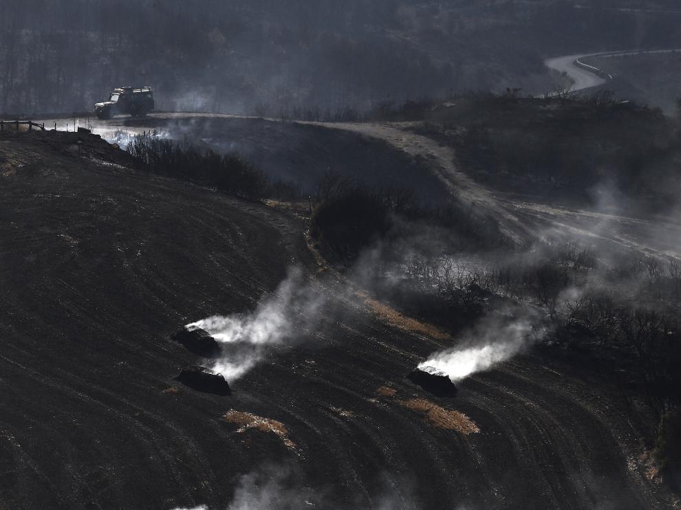 Pacas de paja aún humeantes por el incendio declarado ayer entre las localidades de Tafalla y Pueyo, en Navarra