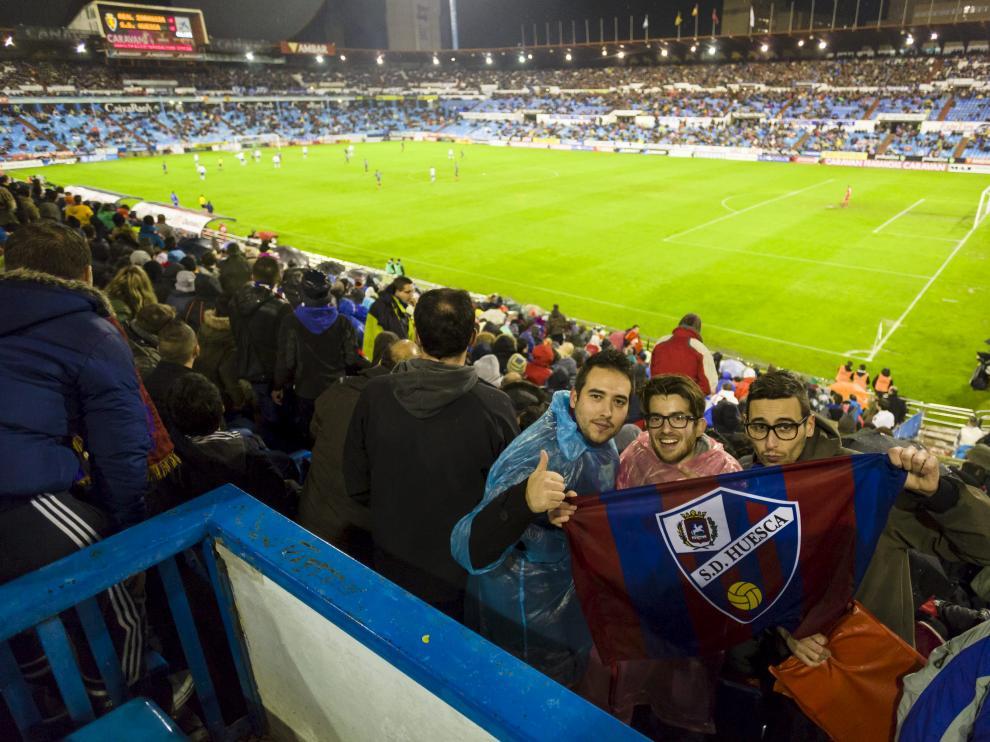 Tres aficionados del Huesca posan en La Romareda en el último derbi