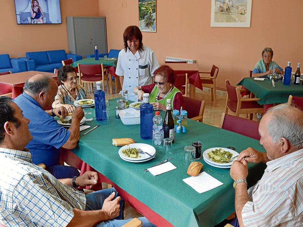 Varios vecinos degustan el menú del comedor para personas mayores de Litago.