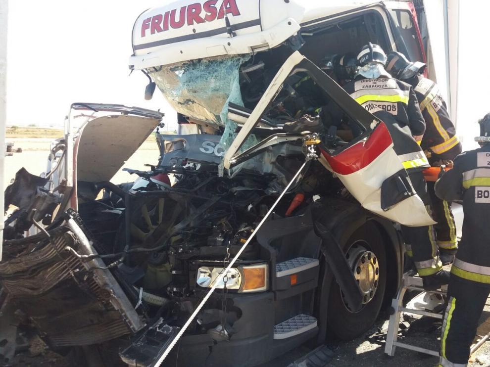 Los bomberos durante la excarcelación del conductor de uno de los camiones.