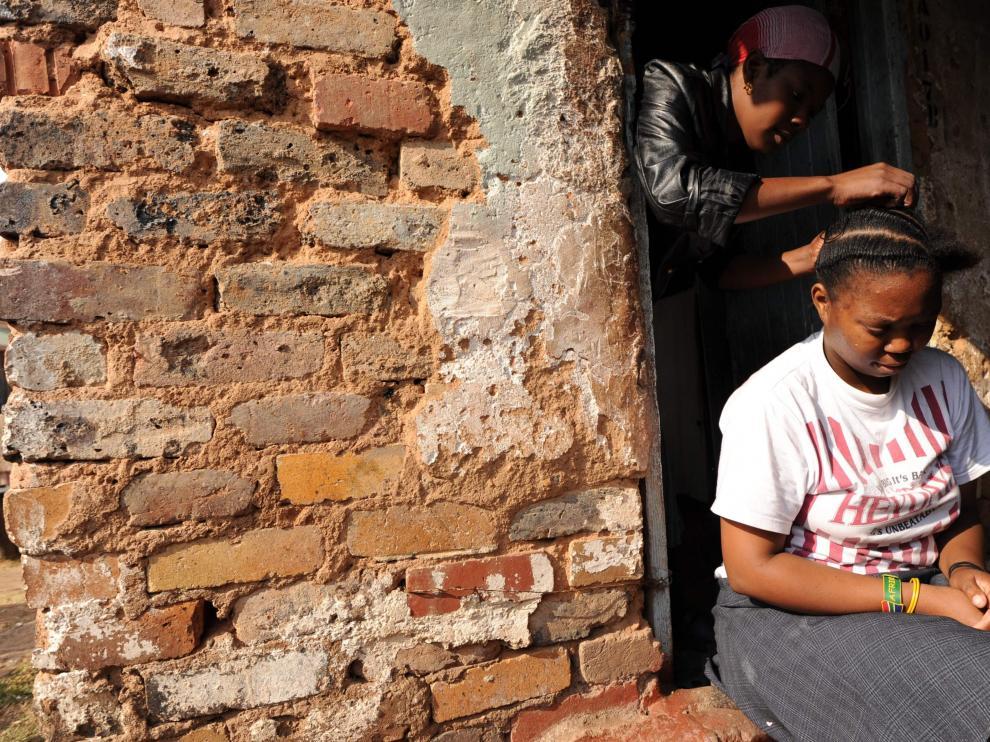 Foto archivo de una mujer haciendo trenzas a una niña en Sudáfrica