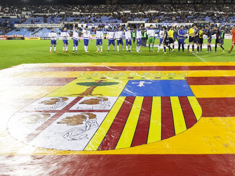 Los jugadores del Real Zaragoza y el Huesca se saludan durante el derbi de la pasada temporada