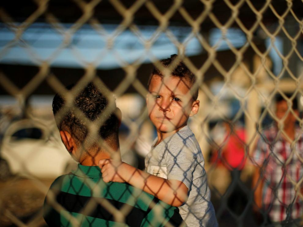Un niño y un joven esperan a sus familiares en la frontera entre la Franja de Gaza y Egipto, abierta durante dos días por cuestiones humanitarias.