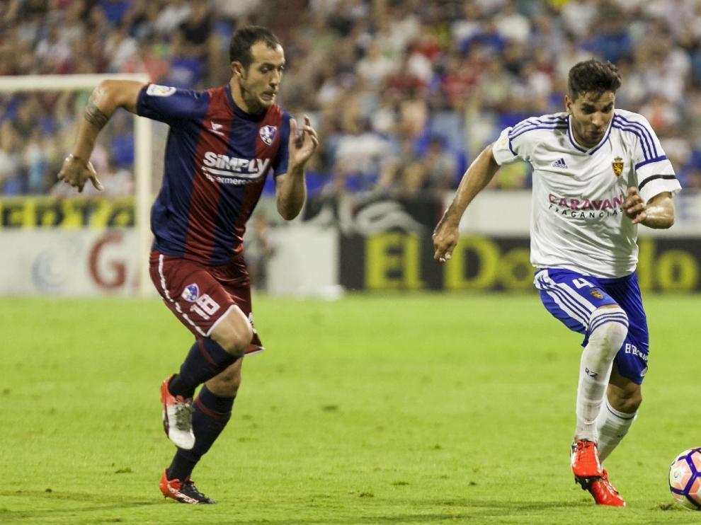 Cabrera, corta un balón ante Urko Vera durante el partido ante el Huesca, donde cayó lesionado con un esguince de tobillo.