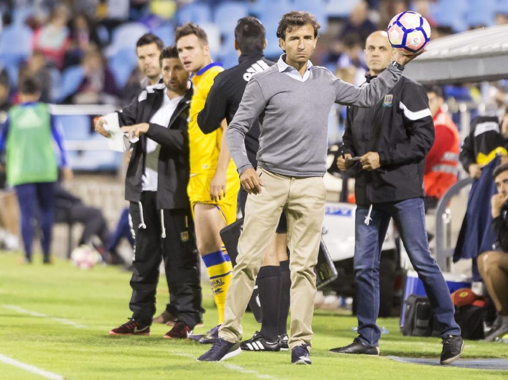 Luis Milla, recoge un balón en su banquillo durante el transcurso del Real Zaragoza-Alcorcón del pasado sábado.