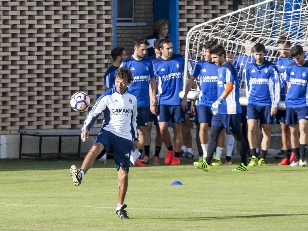 Luis Milla juega con un balón mientras los jugadores trasladan una portería móvil durante el entrenamiento.