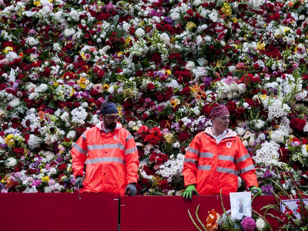 Los jardineros municipales acudieron vestidos con el traje regional y un chubasquero para evitar calarse con las gotas de lluvia que cayeron ayer.
