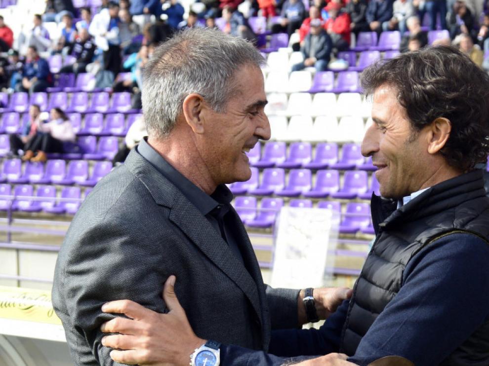Paco Herrera y Luis Milla se saludan el pasado domingo en la banda de Zorrilla, antes del Valladolid-Real Zaragoza. Son el primero y el último entrenador desde que los blanquillos bajaron a Segunda, ahora ya con Agné como nuevo eslabón en la larga lista.