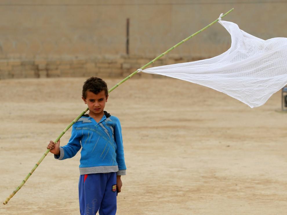 Un niño iraquí porta una bandera blanca en Mosul