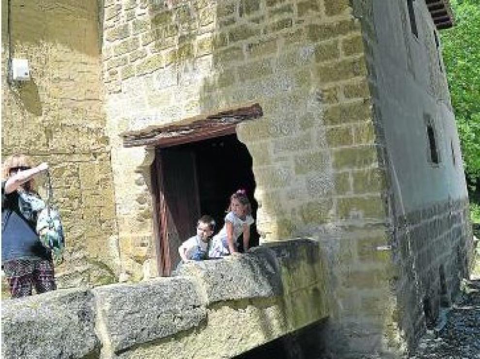 Unos visitantes, junto a la puerta de entrada al Molino.