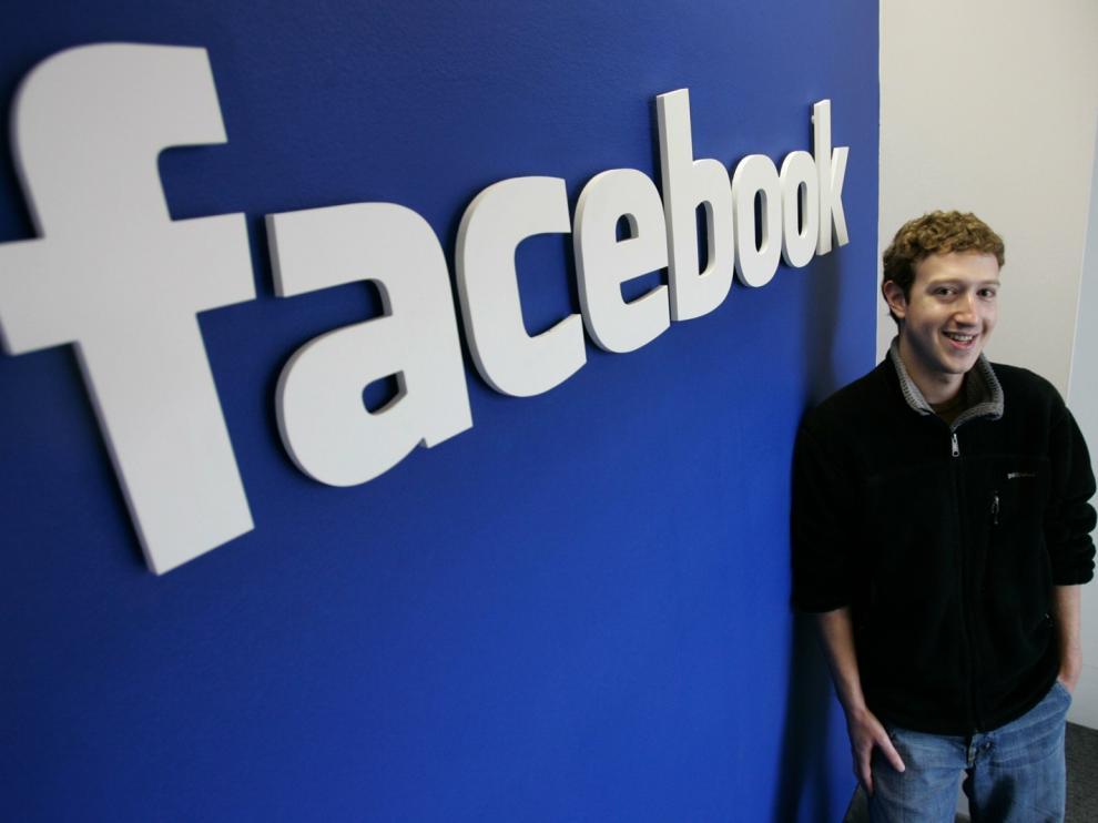 Mark Zuckerberg, ante el logo de Facebook.