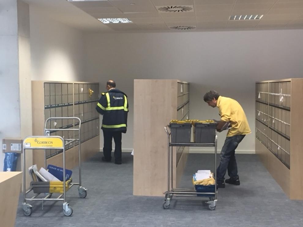 Imagen de dos trabajadores en una oficina de correos.