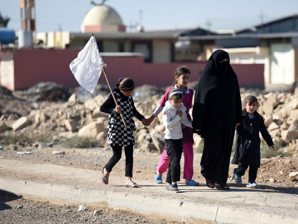 Una mujer y varios niños intentan dejar Mosul alzando una bandera blanca.