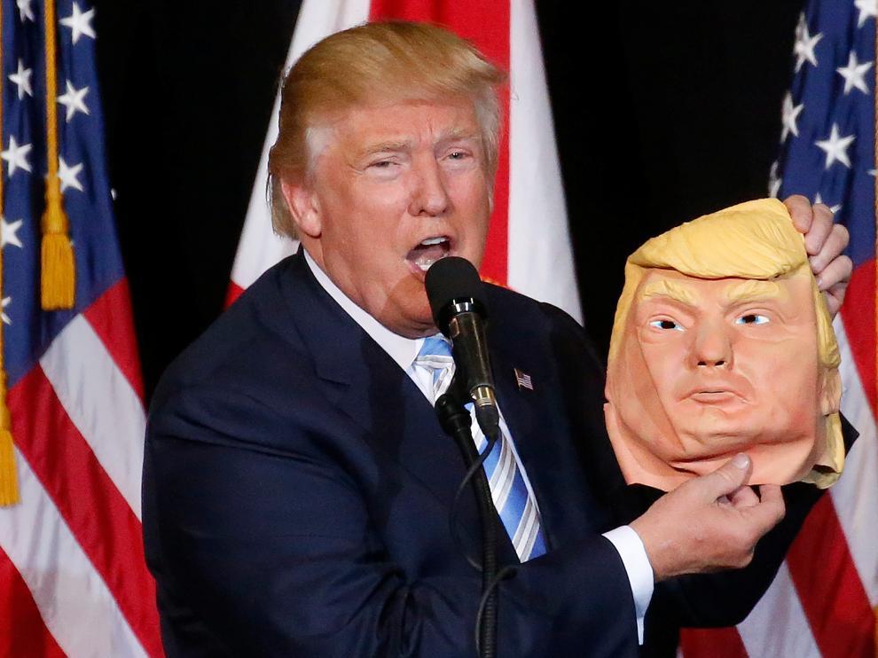 Trump bromeó con una máscara de sí mismo, este lunes en Sarasota.