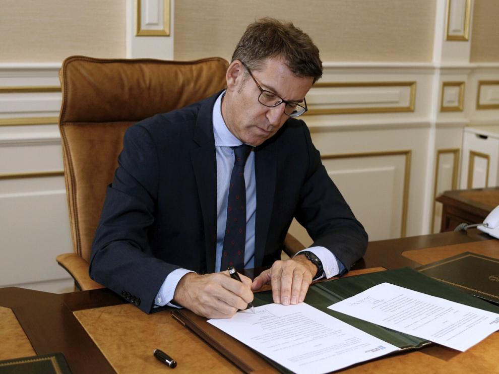 Núñez Feijóo firmando el acta de presidente.