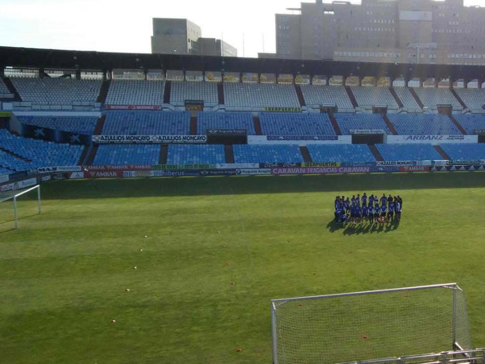 La plantilla del Real Zaragoza, en el habitual corro incial, antes del inicio del entrenamiento de este sábado en La Romareda.