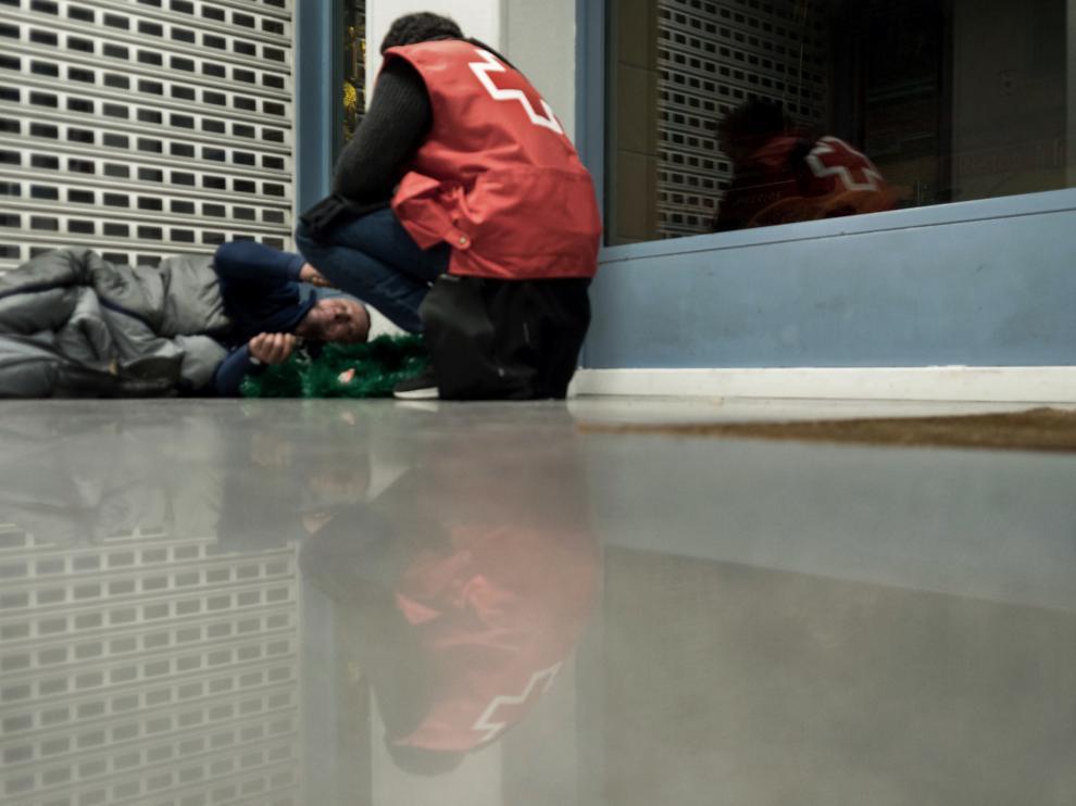 Persona sin hogar en Zaragoza junto a un voluntario de Cruz Roja.