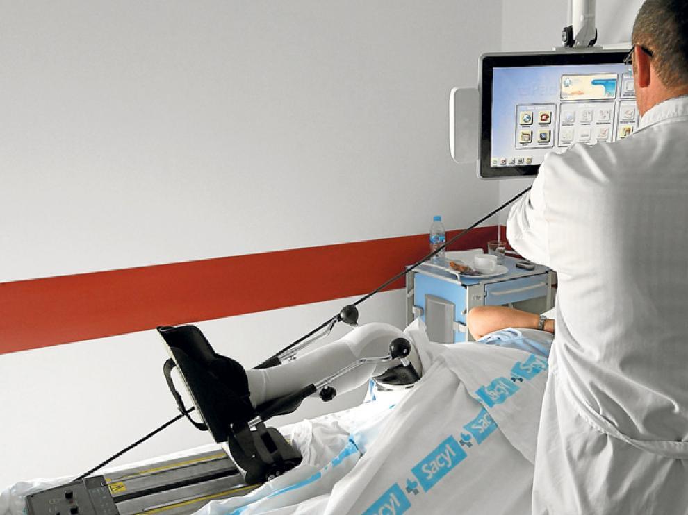 Un profesional sanitario atiende a un paciente ingresado en el Hospital Santa Bárbara.