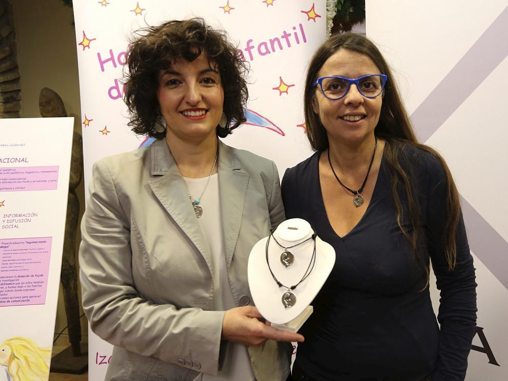 Isabel Claver y Mónica Sarasa, con el collar.