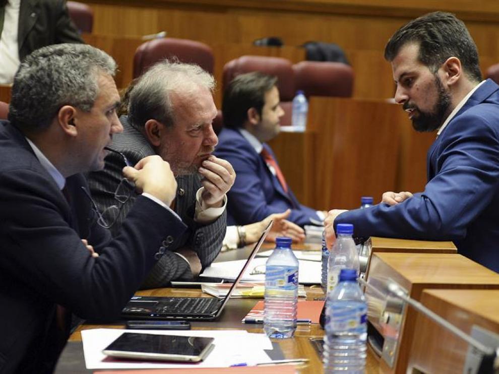 El portavoz del Grupo Parlamentario Socialista, Luis Tudanca (d), conversa con los procuradores Javier Izquierdo (i), y José Francisco Martín (c), durante la sesión plenaria de las Cortes