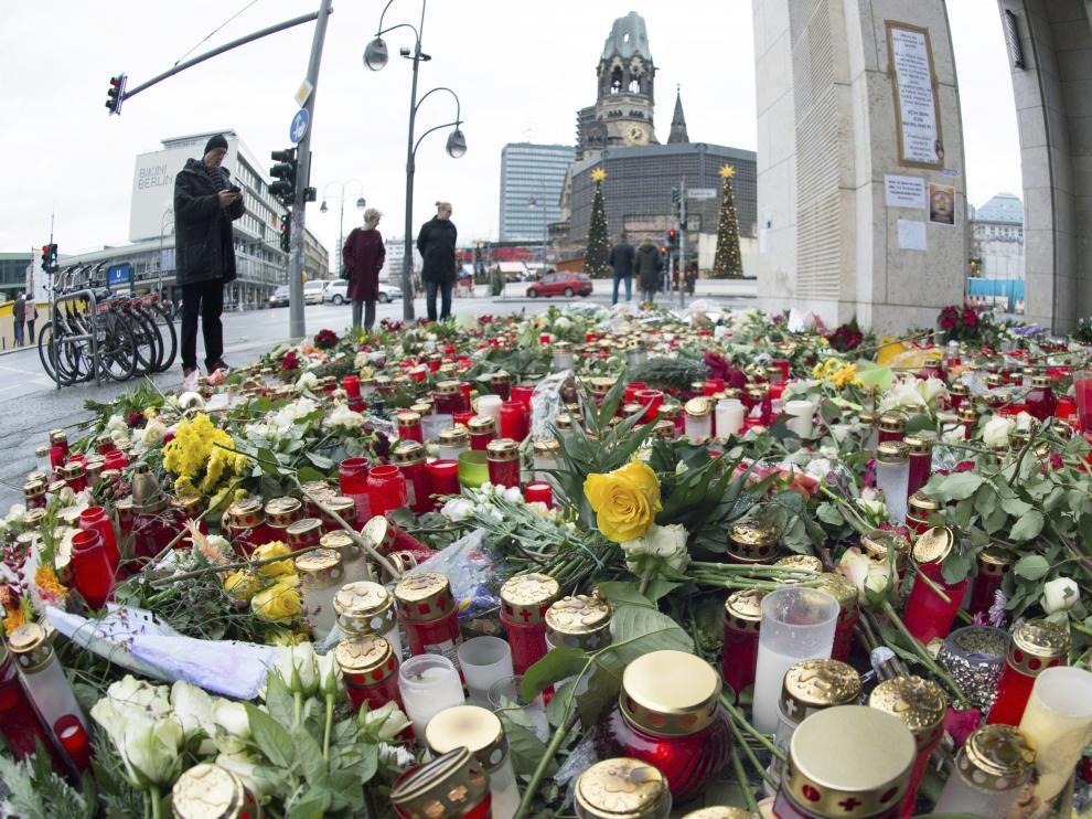 Varias personas pasan junto a las velas y las flores en la plaza Breitscheidplatz.