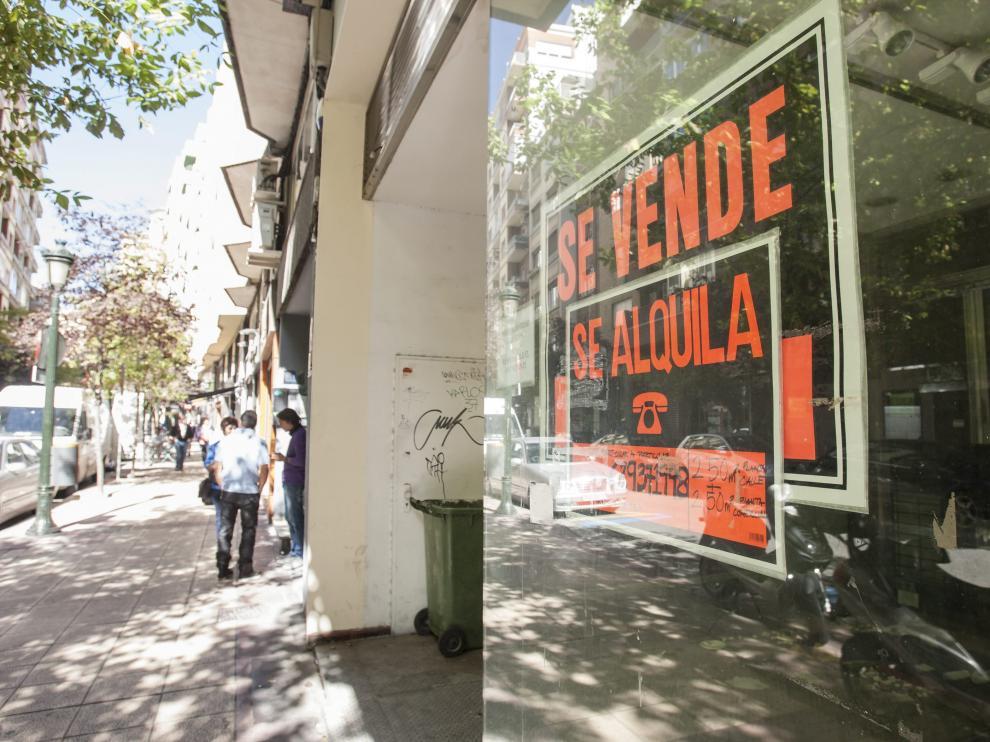Carteles de 'se vende' y 'se alquila' en un local de la zaragozana calle de Francisco de Vitoria.