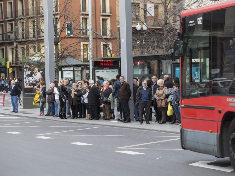 Un grupo de usuarios espera la llegada de un autobús.
