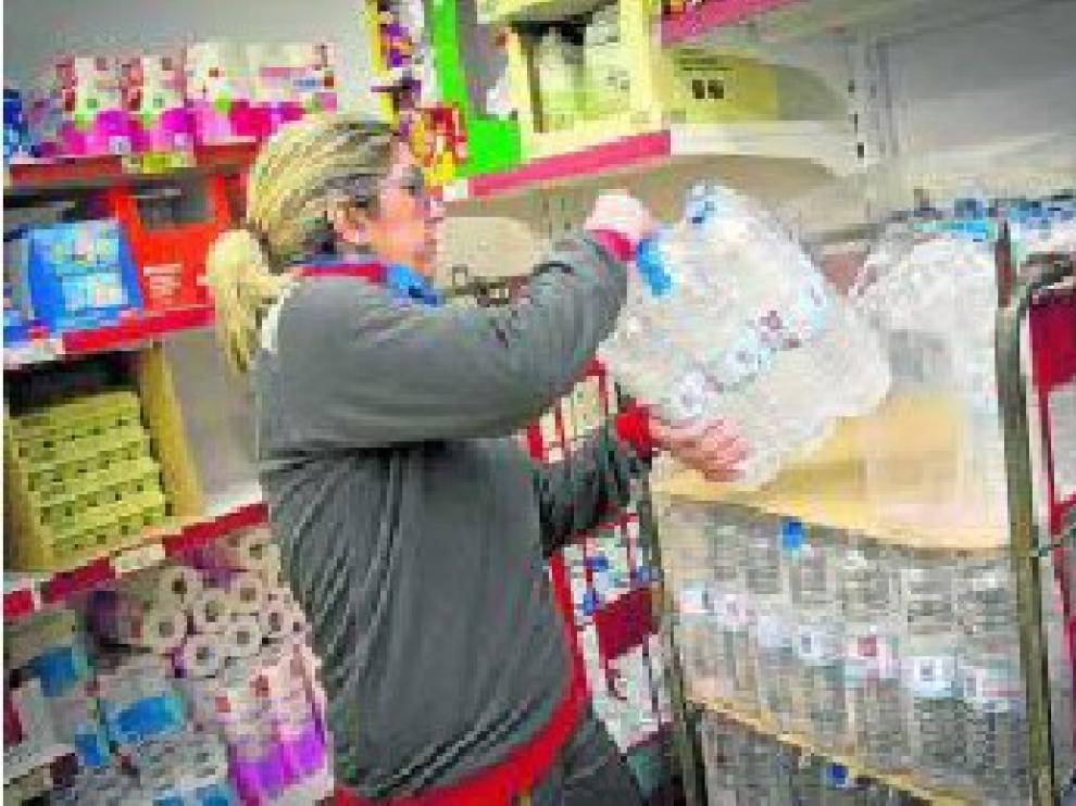 Una empleada del supermercado Dia de Calatorao repone botellas y garrafas de agua.