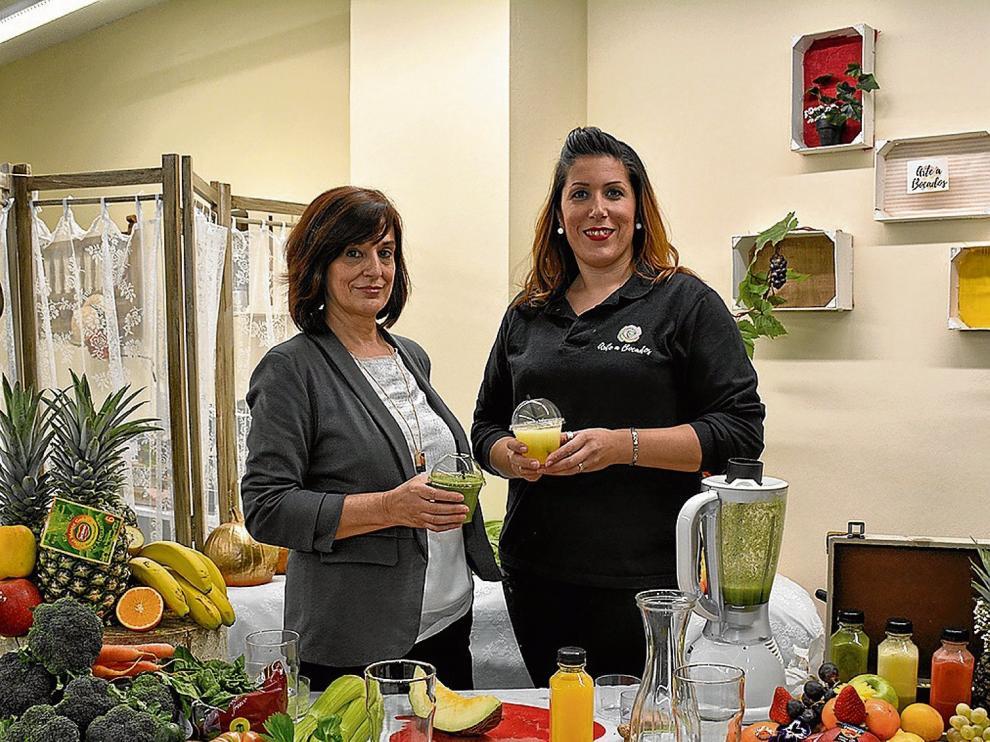 La 'coach' nutricional Asun Armas y Eva Muniesa, propietaria de Arte a Bocados, preparando zumos verdes.