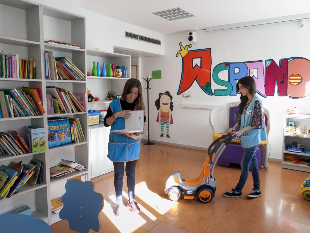 Voluntarios de Aspanoa en la sala de juegos de la planta de Oncopediatría del hospital Infantil.