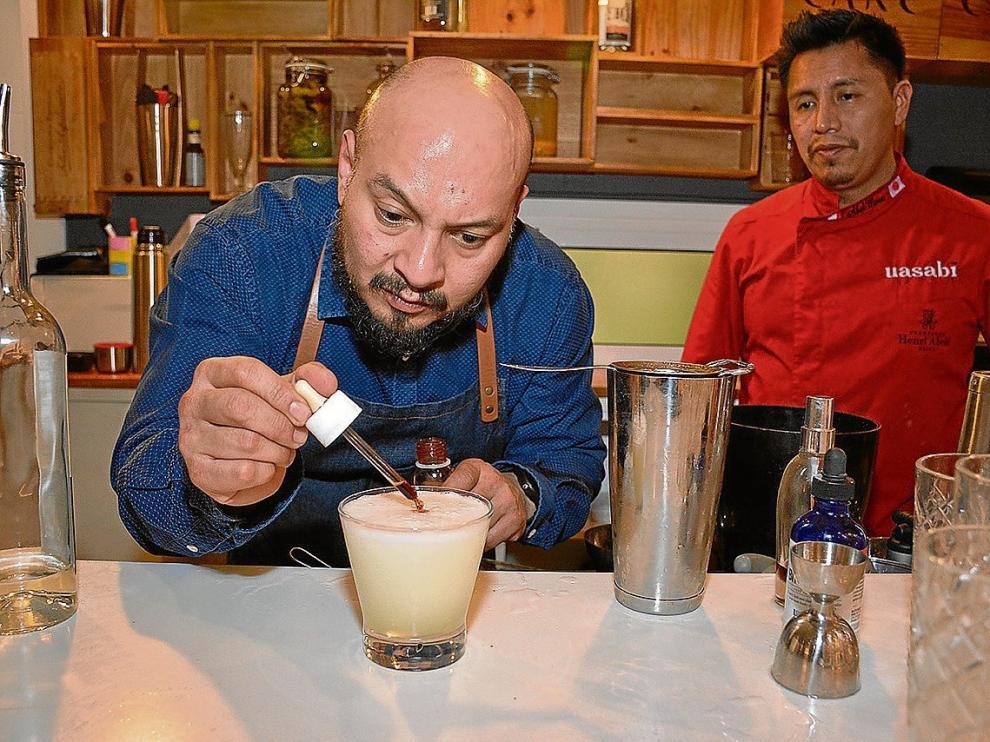 Omar Kuan, añadiendo unas gotas de angostura al pisco sour que preparó en Chilcano.