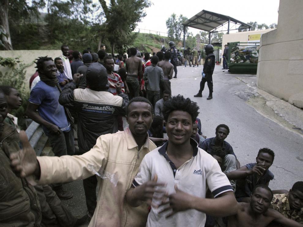 Varios inmigrantes, felices tras saltar valla.