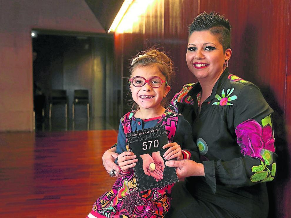 Carol Zaborras, con su hija Libe en brazos, que enseña el libro '570' donde narra su experiencia.